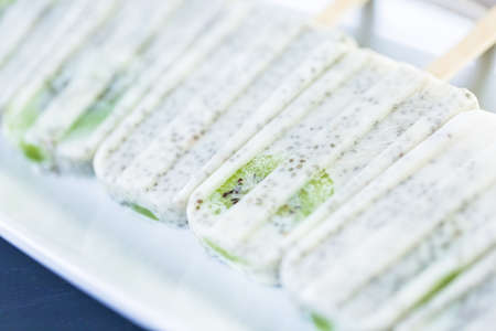 Kiwi coconut chia popsicles on a white serving plate.