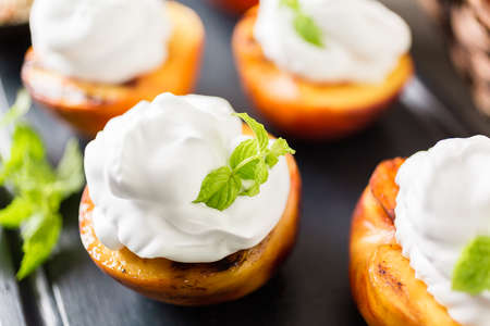 Grilled organic peachs with whipped cream, and garnished with fresh mint. Stock Photo