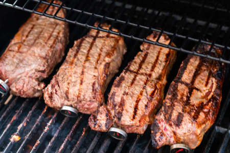 Grilling New York strip steak on outdoor gas grill. 写真素材