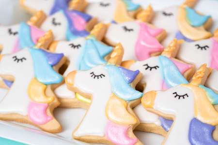 Unicorn sugar cookies decorated with royal icing and food glitter on a blue background. 版權商用圖片