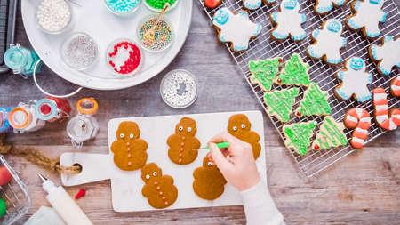 Disposizione piatta. Passo dopo passo. Decorare i biscotti di panpepato e zucchero con la ghiaccia reale per Natale. Archivio Fotografico