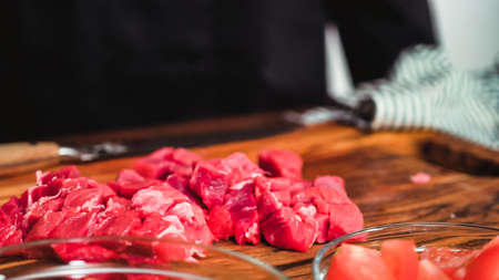Step by step. Slicing beef into the small cubes for beet soup, borscht.