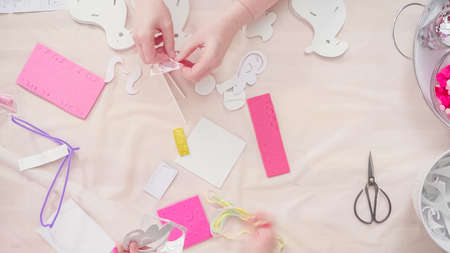 Flat lay. Step by step. Mother and daughter making unicorn craft from paper foam. Фото со стока