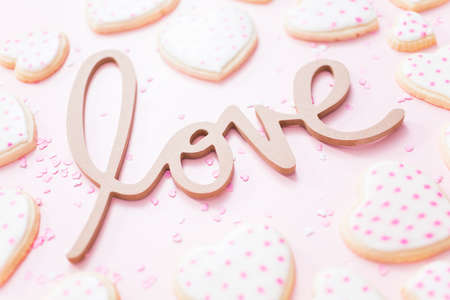 LOVE sign with heart shaped sugar cookies on a pink background.