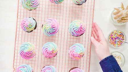 Flach liegen. Schritt für Schritt. Einhorn-Schokoladen-Cupcakes mit regenbogenfarbenem Buttercreme-Zuckerguss. Standard-Bild
