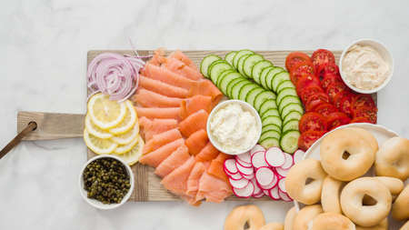 Flat lay. Step by step. Assembling bagel brunch board with smoked salmon and fresh vegetables. Фото со стока
