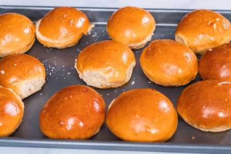 Brioche mini hamburger buns on a baking sheet.