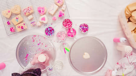 Flat lay. Step by step. Decorating sugar cookies with royal icing and sprinkles for Valentines day. Stock Photo