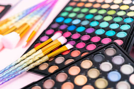 New eyeshadow palette with makeup brushes on a pink background. Banque d'images