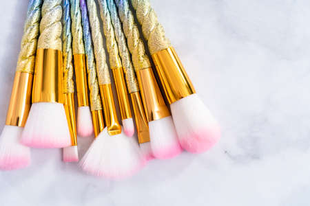 Unicorn color makeup brushes on a marble background.