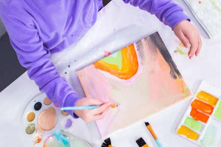 Petite fille peignant sur toile avec de la peinture acrylique.