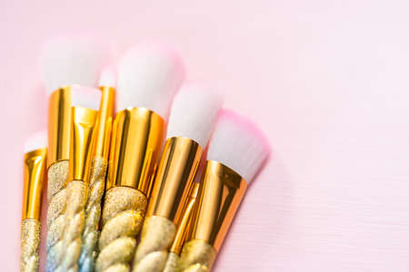 Unicorn color makeup brushes on a pink background.