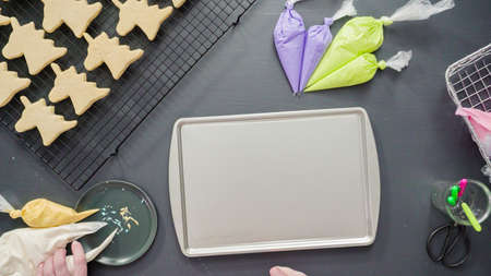 Flat lay. Decorating unicorn sugar cookies with multi-color royal icing.