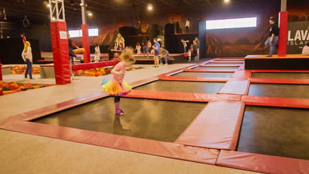 Denver, Colorado, USA-December 28, 2018 - Little girl jumping at the indoor airsport playground. Éditoriale