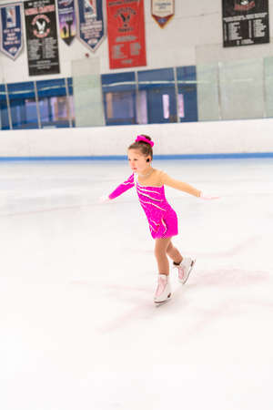 Denver, Colorado, USA-May 14, 2019 - Little figure skater in competition dress practicing her program on the indoor ice rink.