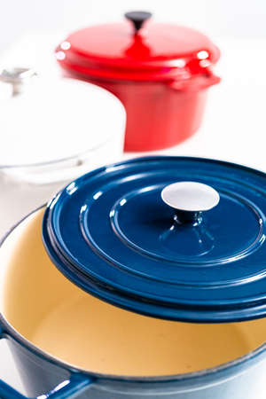 Red, white and blue enameled cast iron covered round dutch ovens on a whjite background.