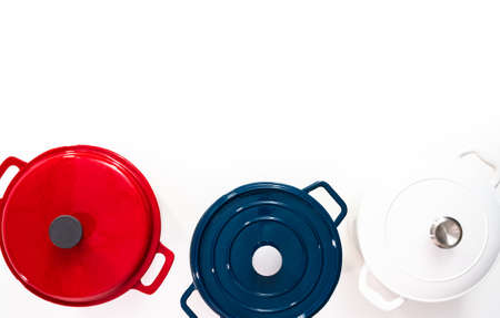 Flat lay. Red, white and blue enameled cast iron covered round dutch ovens on a whjite background.