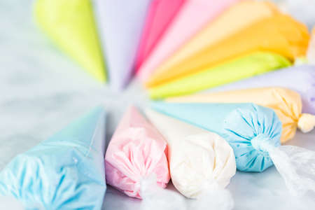 Piping bags with pastel color royal icing to decorate Easter sugar cookies.