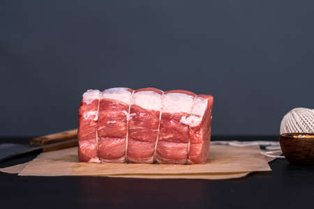 Uncooked boneless pork roast on the brown butcher paper.