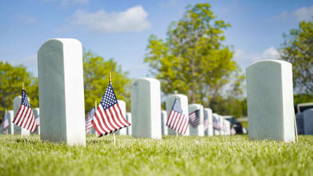 Small American Flags next to white marble gravestones at the Fort Logan National Cemetery on Memorial Day.