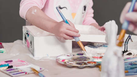 Painting with a white acrylic paint unicorn paper mache figurine.
