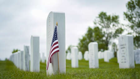 Denver, Colorado, USA-May 26, 2019 - Small American Flags next to white marble gravestones at the  Fort Logan National Cemetery on Memorial Day. Éditoriale