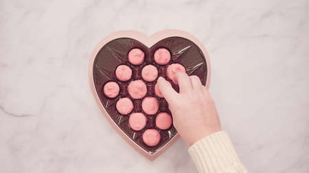 Flat lay. Heart shaped box of pink chocolated for Valentine's Day. Imagens