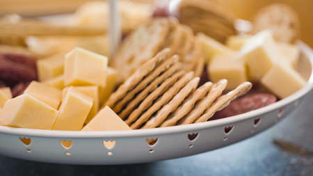 Appetizer plate with crackers, salami, and cheese.