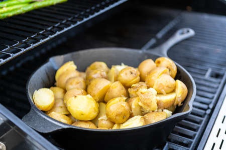 Frying small golden potatoes in cast iron skillet an outdoor gas grill.