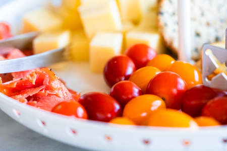 A white tiered platter filled with smoked salmon, cheese, crackers, and fresh fruits and berries.