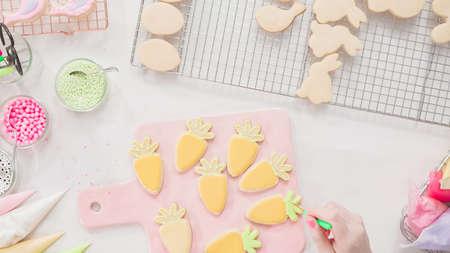 Passo dopo passo. Disposizione piatta. Decorare i biscotti di zucchero di Pasqua con la glassa rotal. Archivio Fotografico