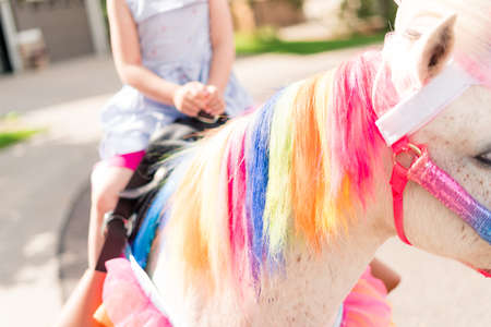 Kleines Mädchen, das auf der Geburtstagsfeier des kleinen Mädchens ein Einhorn reitet.