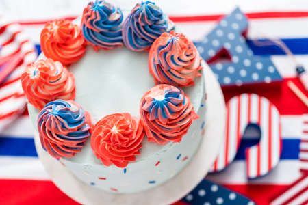 Red, white, and blue round vanilla cake with buttercream frosting for July 4th celebration.