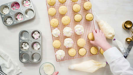 Flat lay. Step by step. Decorating vanilla cupcakes with white buttercream frosting for Easter.