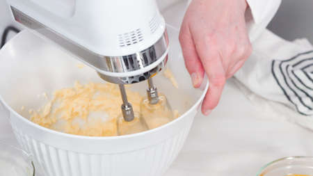 Step by step. Mixing batter to bake vanilla cupcakes with buttercream frosting.
