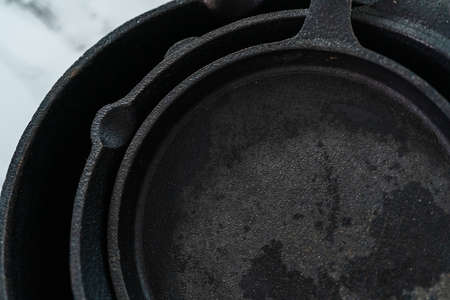 Close up view. Variety of cast iron frying pans on a marble background. 免版税图像