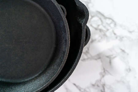 Close up view. Variety of cast iron frying pans on a marble background. Фото со стока
