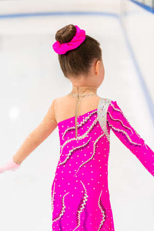 Little figure skater in pink dress practicing on the indoor ice rink.
