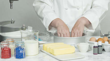 Step by step. Greasing cake pans with butter to bake a three-layer vanilla cake.