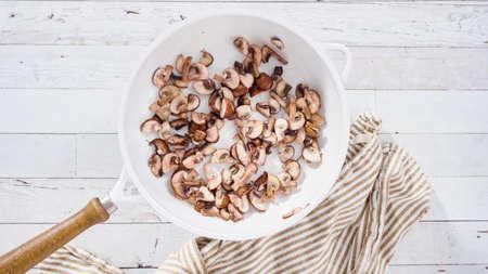 Flat lay. Sauteed organic baby bella mushrooms in a white frying pan.