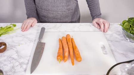 Curring vegetables on a white cutting board to cook vegetarian white bean soup. Stock Photo