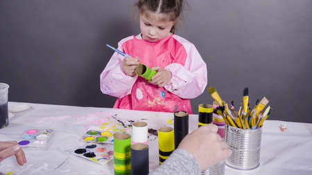 Kids papercraft. Painting empty toilet paper rolls with acrylic paint to create paper bugs.