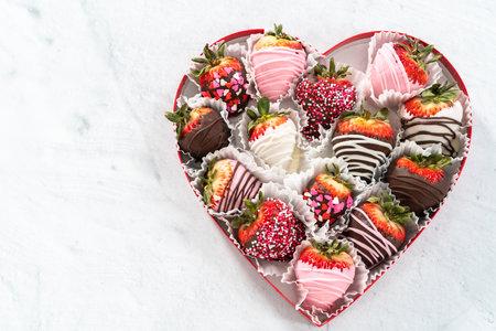 心形盒子,白色背景上有各式各样的巧克力覆盖草莓。