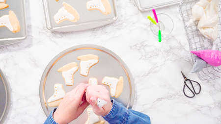 Flat lay. Decorating ice skate shaped sugar cookies with black color royal icing.