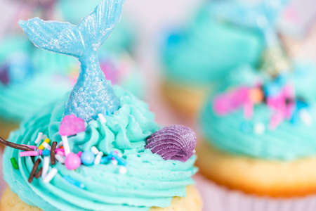 Gourmet mermaid cupcakes topped with blue buttercream frosting and decorated with sprinkles and chocolate mermaid tails.