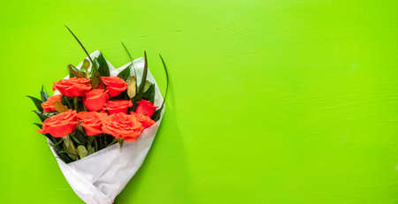Flat lay. Bouquet of red roses and green leaves on a green background. 写真素材 - 167165273