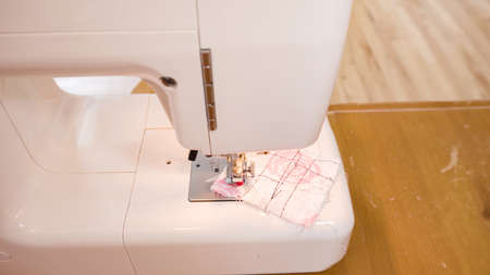 Sewing cotton face mask with a sewing machine for coronavirus outbreak.