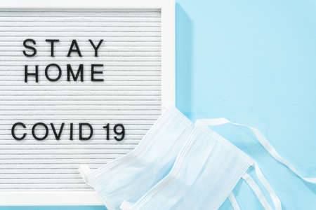 STAY HOME and COVID-19 sign on message board with a blue medical mask. Archivio Fotografico