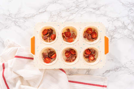 Flat lay. Filling silicone muffin pan with ingredients to bake bacon and cheese egg muffin.