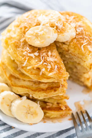 Eating freshly baked coconut banana pancakes garnished with sliced bananas and toasted coconut.